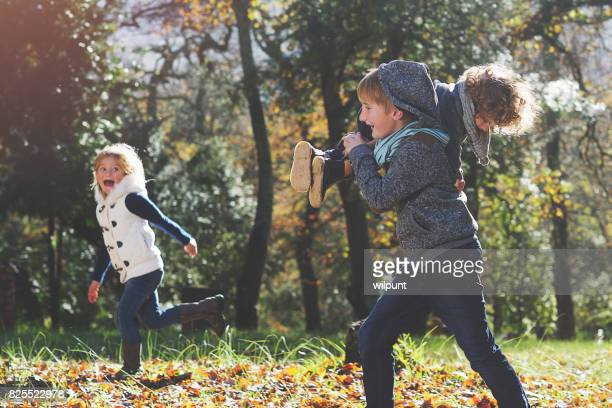 boy carrying brother chasing sister - kids playing tag stock photos and pictures