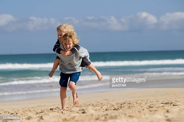 Boy carrying brother piggyback on beach