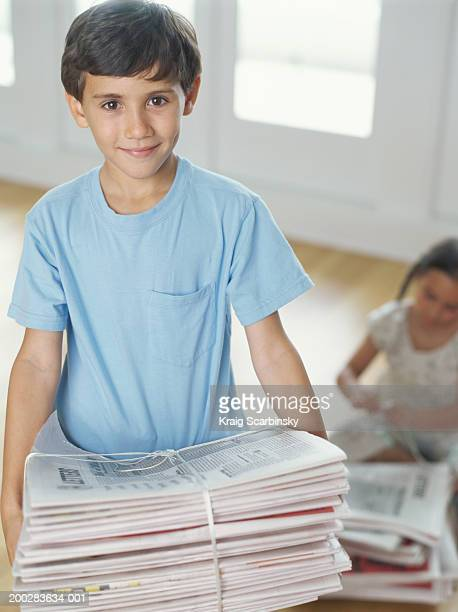 Boy (6 )用のバンドルの新聞、笑顔、ポートレート