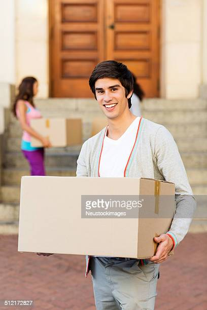 Boy Carrying Cardboard Box With Friend Standing In Background