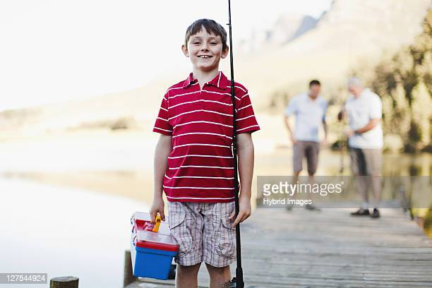 Boy carrying fishing rod on jetty