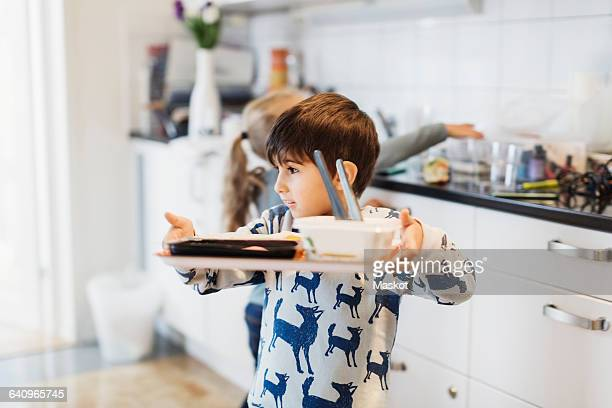 Boy carrying food tray in preschool