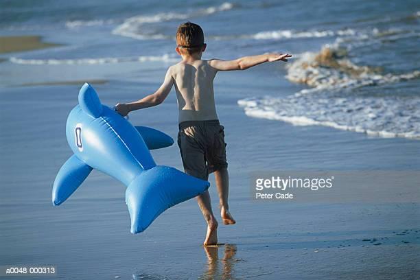 boy carrying inflatable toy - knaben in badehosen stock-fotos und bilder
