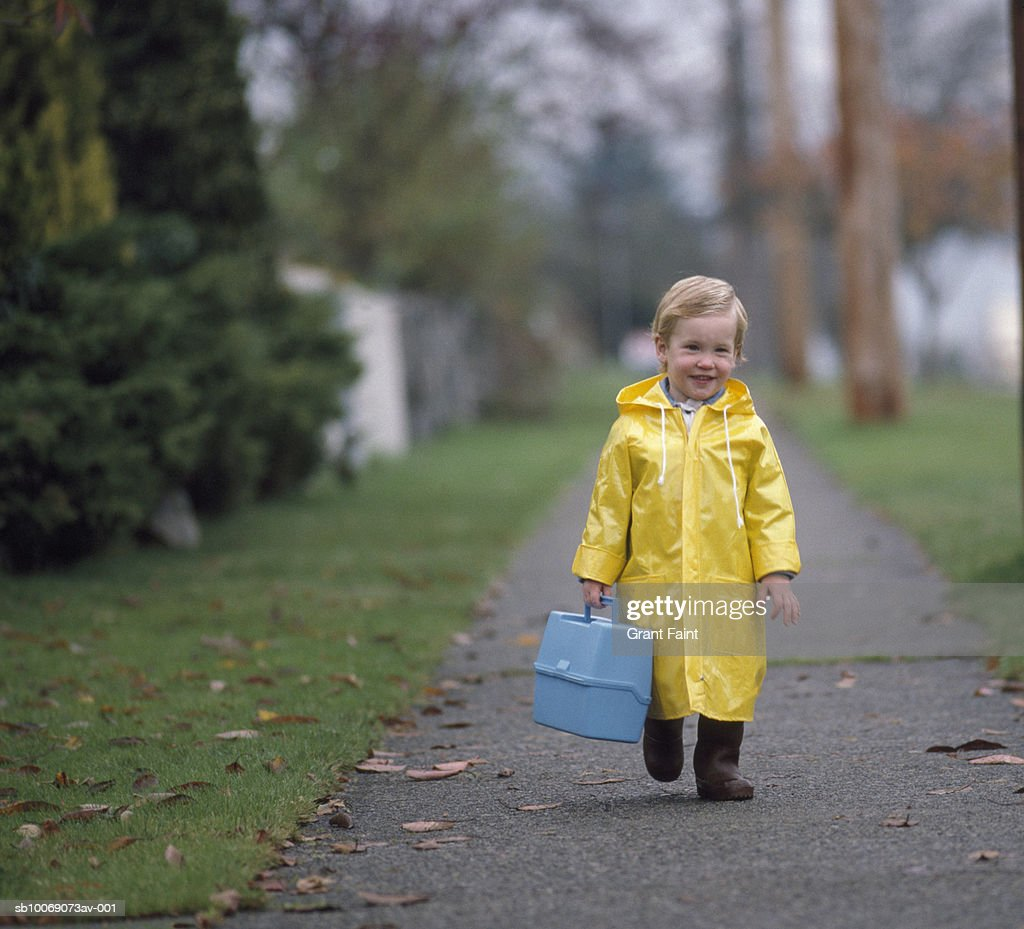 Boy (2-3) carrying plastic lunch box, walking on footpath, portrait : Stockfoto