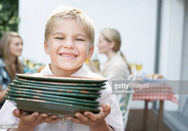 Boy carrying plates to picnic