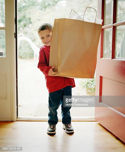 Boy (3-5) carrying shopping bag into house, portrait