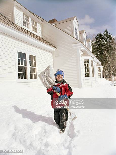 boy (7-9) carrying snow shovel in back yard, portrait, winter - snow shovel stock pictures, royalty-free photos & images