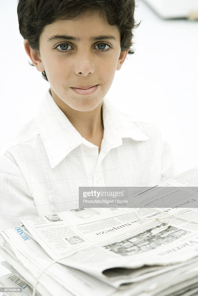 Boy carrying stack of newspapers, smiling at camera : Stock Photo