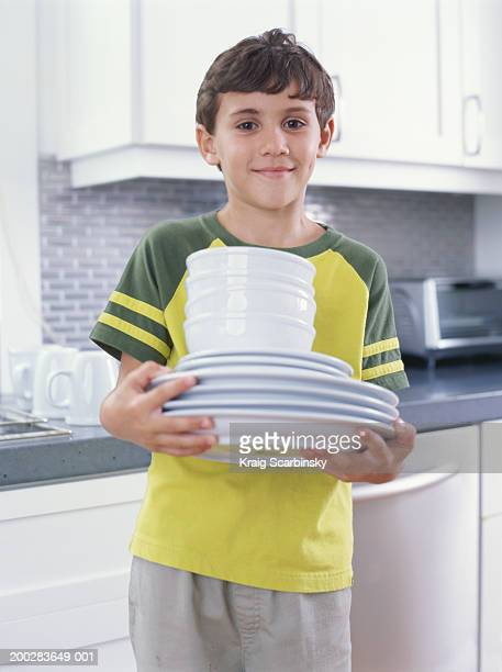 Boy (6-8) carrying stack of plates and bowls, smiling, portrait