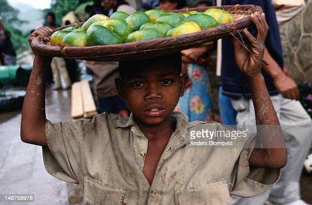 Boy carrying tray of mandarins for sale on head.