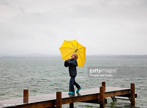 Boy carrying umbrella on wooden dock