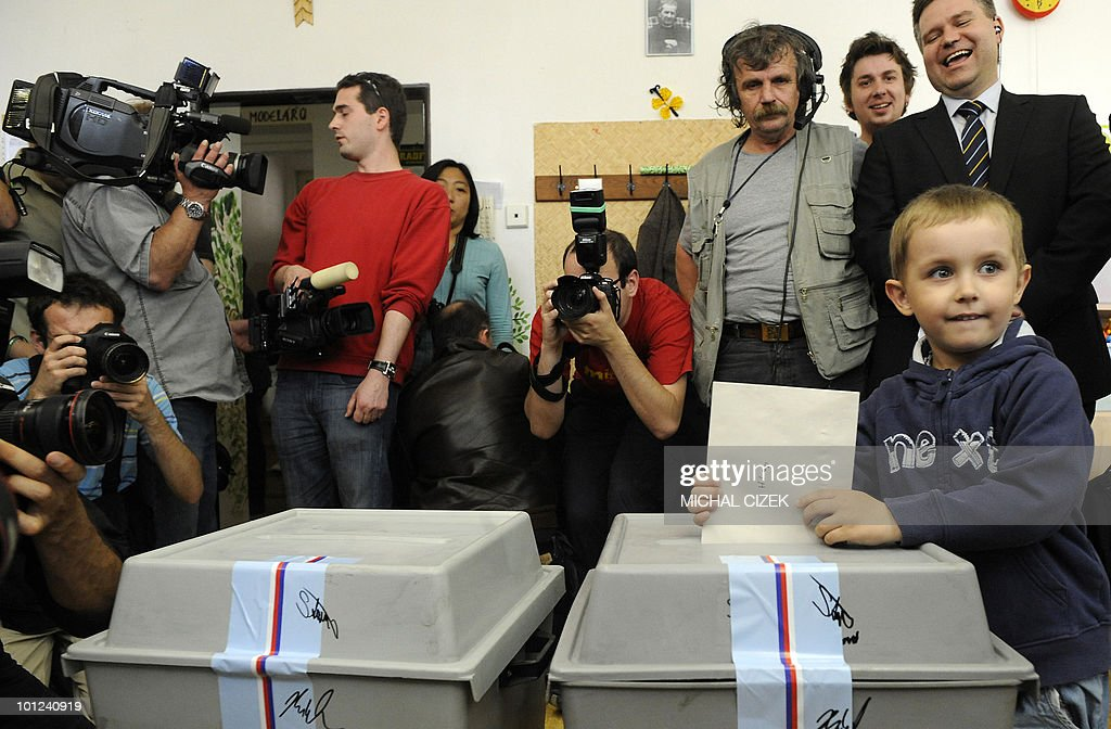A boy casts the ballot of his mother at a polling station on May 28, 2010 in Prague on the first day of the Czech elections. Czech voters headed to the polls to choose new leaders and bring an end to a lengthy political limbo triggered by the collapse of a centre-right coalition more than a year ago.