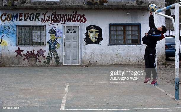 A boy catches a ball at a goal in front of a mural of revolutionary leader Argentineborn Ernesto Che Guevara in Villa Zabaleta shantytown in Buenos...