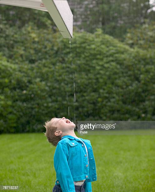 Boy Catching Raindrops from Eaves in His Mouth