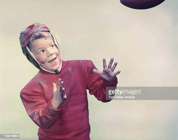 Boy catching rugby ball, smiling