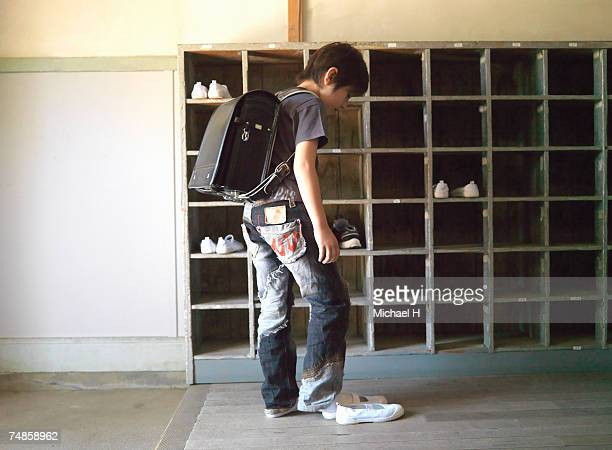 boy (6-7) changing shoes at school - young boys changing in locker room stock pictures, royalty-free photos & images