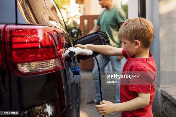 Boy charging electric car against father standing by house
