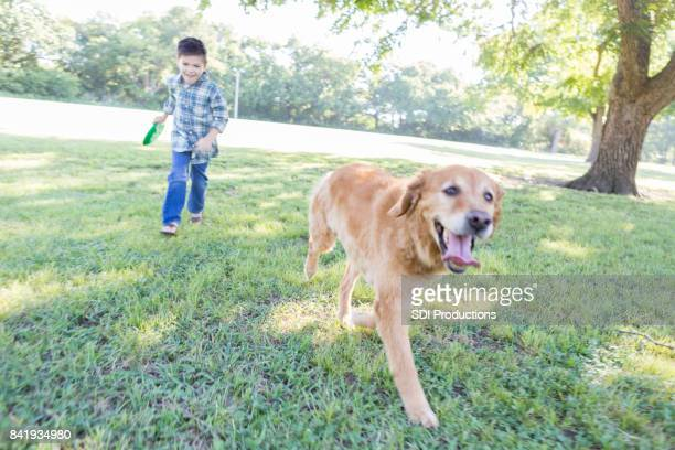 Boy chases dog while playing in the park