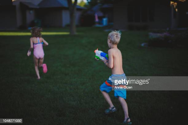 Boy chases girl while holding a squirt gun