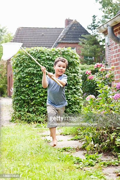 Boy chasing butterflies with net