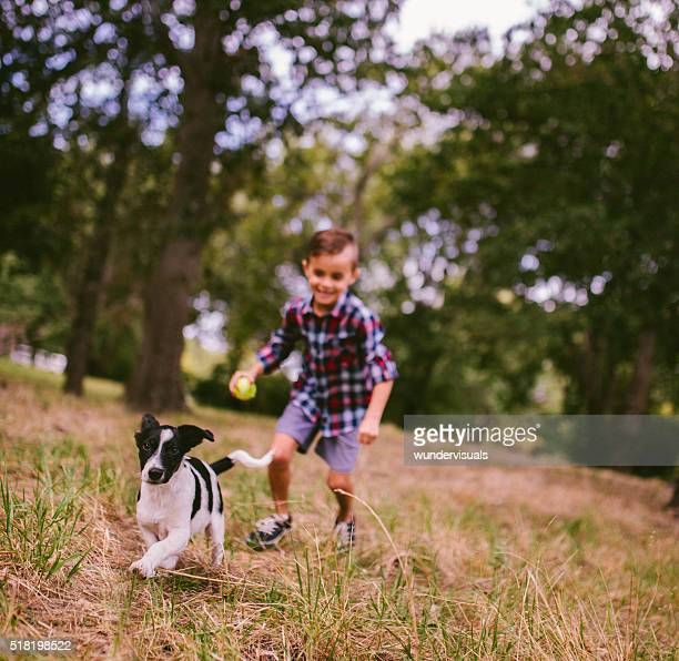 Boy chasing his running puppy dog in park with ball