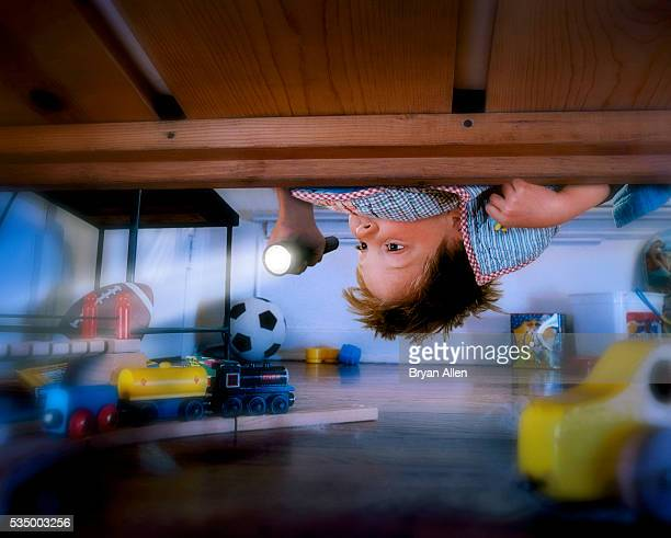 Boy Checking Under Bed with Flashlight
