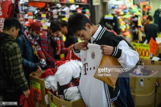 A boy checks the size of a football tshirt on sale at a discount stall in Ameya Yokocho market on January 4 2018 in Tokyo Japan Ameya Yokocho claimed...