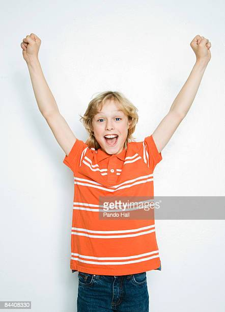 Boy (10-11) cheering, arms up, smiling