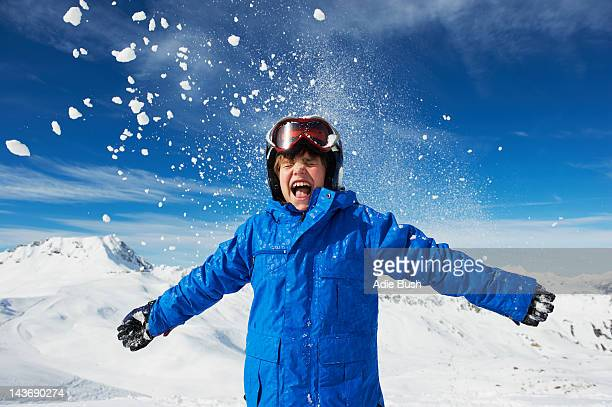 Boy cheering on snowy mountaintop