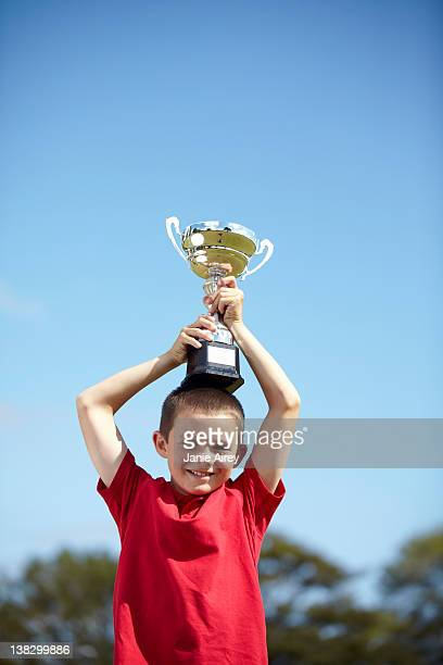 boy cheering with trophy outdoors - holding trophy stock pictures, royalty-free photos & images