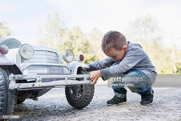 boy child controlling wheel model toy vintage car - spaß stock pictures, royalty-free photos & images