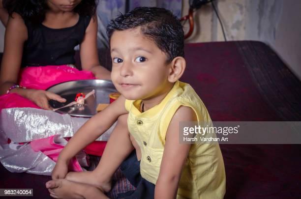 boy child looking at camera excitingly while sitting with her si - segunda feira - fotografias e filmes do acervo
