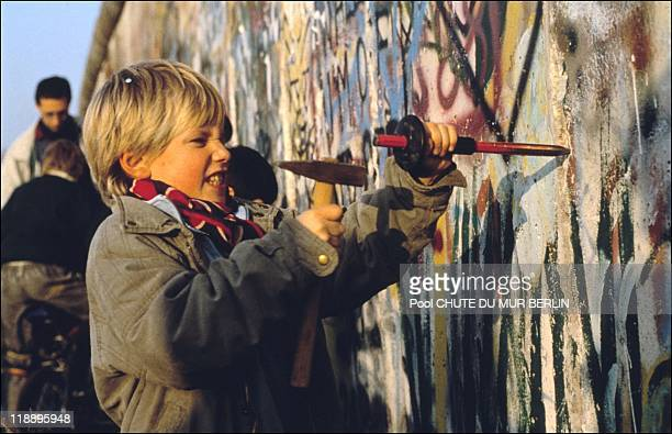 Boy chips at the Berlin wall on November 12, 1989 in Berlin, Germany.