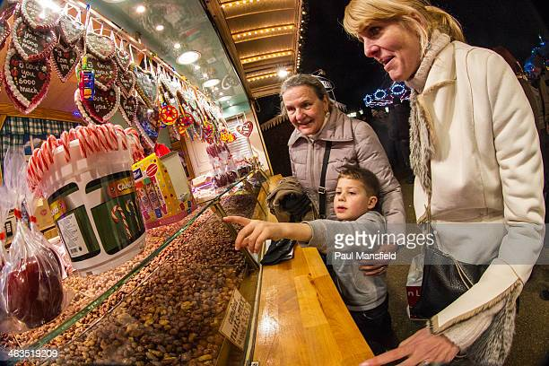 CONTENT] A boy chooses some sweets with his mother and grandmother looking on This was at a mobile stall at Winter Wonderland Hyde Park London