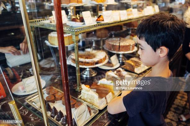 boy choosing a cake to eat - peter lourenco stock pictures, royalty-free photos & images