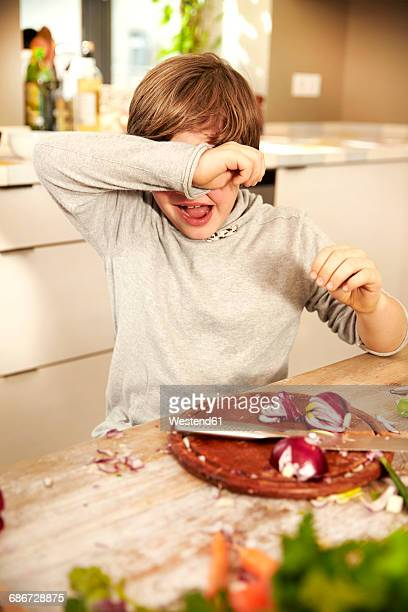 Boy chopping onions covering his eyes
