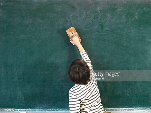 Boy (6-7) cleaning blackboard in classroom