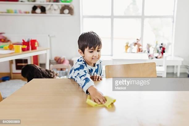 boy cleaning dining table at day care center - tidy room stock pictures, royalty-free photos & images