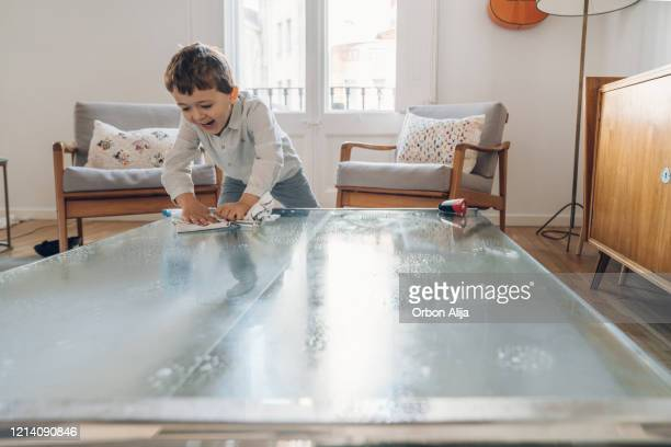 boy cleaning table on living room - tidy room stock pictures, royalty-free photos & images