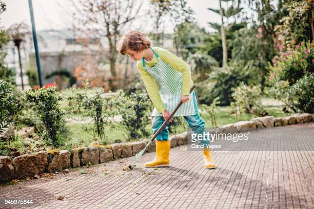boy cleaning up leaves with rake - kids with cleaning rubber gloves stock pictures, royalty-free photos & images