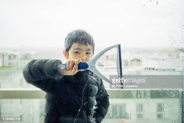 boy cleaning window - peter lourenco photos et images de collection
