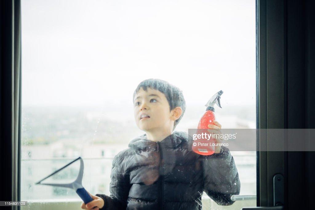 Boy cleaning window : Stock Photo