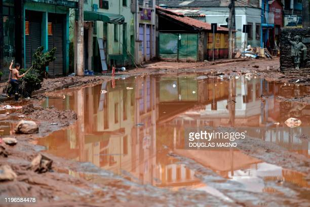 Boy cleans a sidewalk after the overflowing of the Das Velhas River in Sabara, Belo Horizonte, Minas Gerais state, Brazil, on January 26 after heavy...