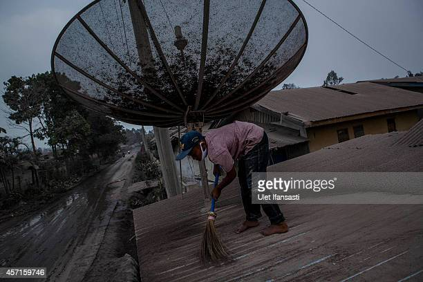 A boy cleans his house as their village is hit by ash from the eruption of Mount Sinabung on October 13 2014 in Berastagi Karo district North Sumatra...