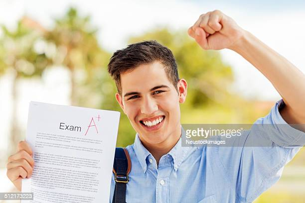 Boy Clenching Fist While Showing Test Result With A+ Grade