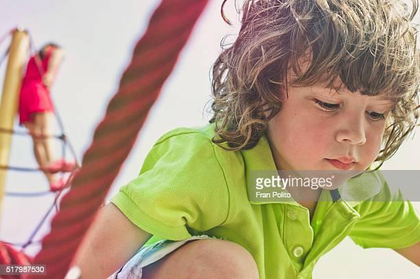 Boy climbing a jungle gym at the playground.