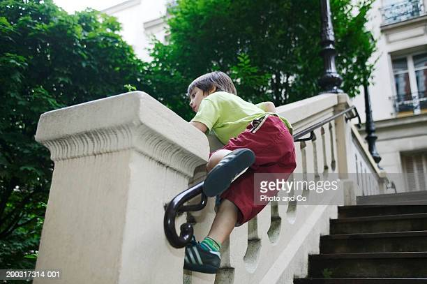 Boy (4-6) climbing bannister wall of steps outside house