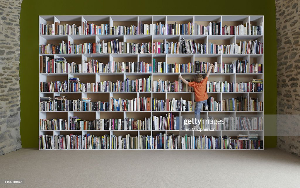 Boy climbing bookshelves : Stock Photo