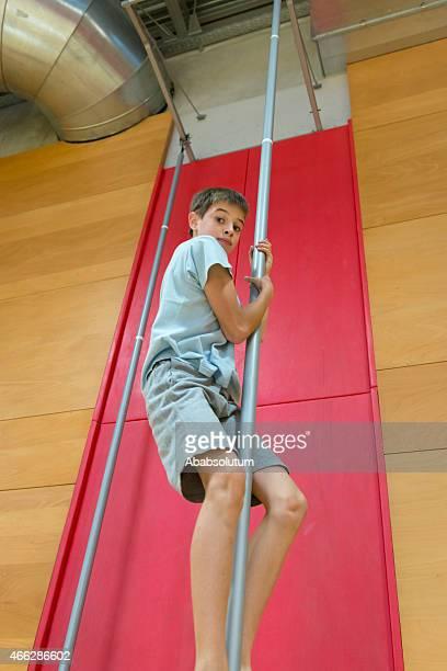 Boy Climbing, Hanging on Vertical Pole in School Gymnasium