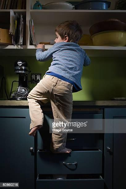 boy climbing in kitchen - danger photos et images de collection